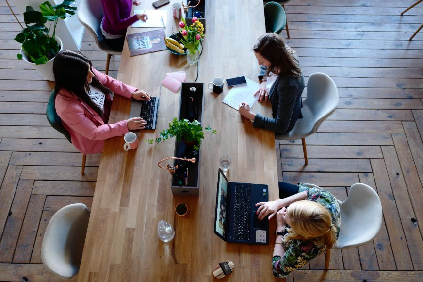 Three woman sitting around a table in a co-working space