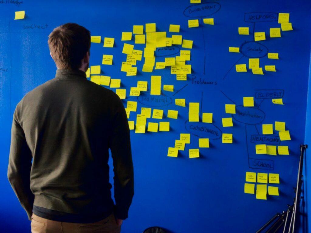 Man staring at a wall full of post it notes