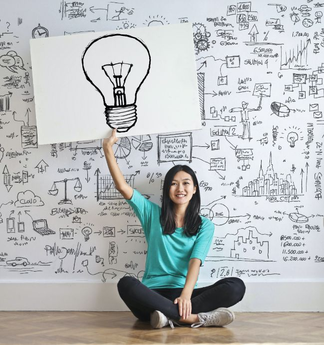 Woman sitting on the floor holding up a drawing of a light bulb